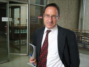 Daniel Horowitz in front of courthouse holiding file for chiropractic fraud case