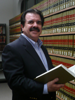 Horowitz personal injury medical consultant, Chiropractor & Paralegal Michael Yates in a suit holding a law book. This picture links to the board of chiropractic examiners website showing dr yates license as valid and active