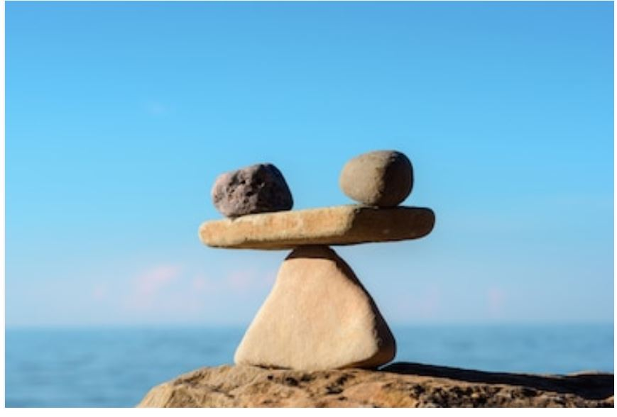 two stones balanced on a rock fulcrum by the ocean illustrating chiropractic balance